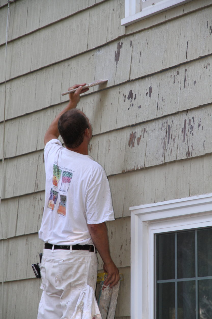 painter scraping a house