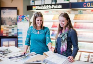 A Hirshfield's staff member looking through sample books with a customer at a retail store, in front of a Hirshfield's Paints sign and paint color chips stand.