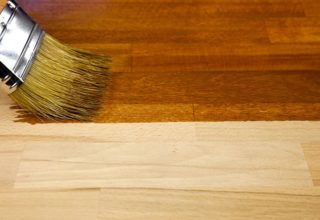 A brush staining a piece of wood.