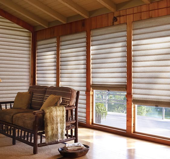 A brown couch sits in front of four large windows with wooden trim and light grey Hunter Douglas roller window shades.
